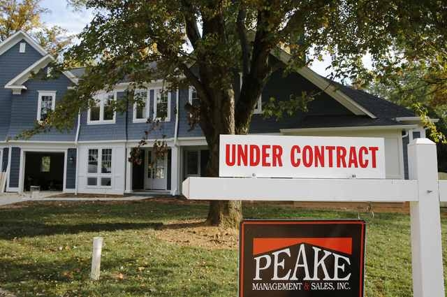 """A real estate sign advertising a home """"Under Contract"""" is pictured in Vienna, Va., outside of Washington, October 20, 2014. U.S. home resales raced to a one-year high in September, the latest indi ..."""