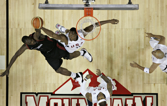 NBA basketball player Joel Anthony, left, with the Miami Heat, who is playing for Team Canada, battles for the rebound against fellow NBA player Dwight Howard with the Orlando Magic, who is playin ...