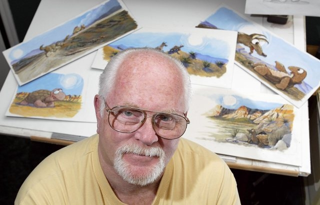Artist Mike Miller poses for a portrait in his Las Vegas home, Thursday, Dec. 18, 2003. Behind him are colored illustrations for his Tomas the Desert Tortoise children's books. (John Locher/Las Ve ...