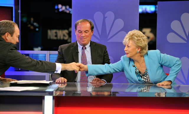 """Television host Jon Ralson, left, shakes the hand of Nevada treasurer Democrat candidate Kim Wallins, right, as her opponent, Republican Dan Schwartz, looks on after their debate on the """"Rals ..."""