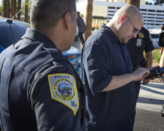 Uber driver Michael Elsner, right, calls an Uber representive after being detained by law enforcement officers in front of the Fashion Show on Friday, Oct. 24, 2014. Local law enforcement officers ...