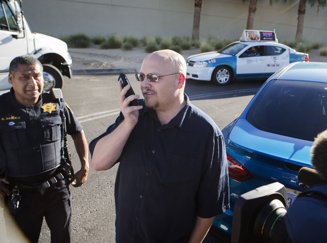 Uber driver Michael Elsner, right, calls an Uber representive after being detained by law enforcement officers in front of the Fashion Show  on Friday, Oct. 24, 2014. Local law enforcement officer ...