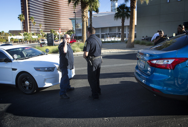 Uber driver Michael Elsner, left, calls an Uber representive after being detained by law enforcement officers in front of the Fashion Show  on Friday, Oct. 24, 2014. (Jeff Scheid/Las Vegas Review- ...