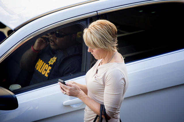Lee Haney with Rogich Communications with a law enforcement officer during a Uber sting operation in front of the Fashion Show  on Friday, Oct. 24, 2014. Local law enforcement officers are ticketi ...