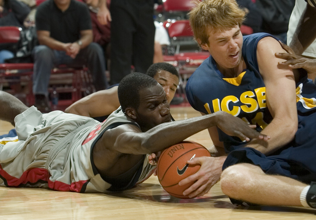 Joel Anthony of UNLV, left, and Chris Devine of UC Santa Barbara battle for the ball on the ground during the first half of their basketball game at UNLV in Las Vegas Friday, Nov. 17, 2006. (John  ...
