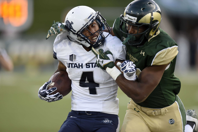 Colorado State safety Trent Matthews (16) tackles Utah State wide receiver Hunter Sharp (4) the first quarter at Hughes Stadium in Fort Collins on Oct 18, 2014. (Ron Chenoy-USA TODAY Sports)