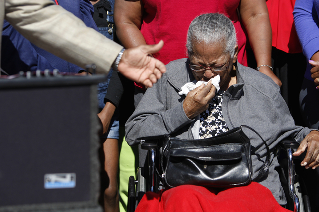 Mary Leach wipes away tears during a press conference for a newly installed crosswalk traffic light at the intersection of Martin Luther King Boulevard and Balzar Avenue, near the area where her s ...