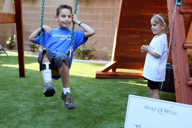 Vinnie Huebner, 9, left, smiles while swinging on his new playground during a Make-A-Wish reveal event Saturday, Oct. 4, 2014, in Las Vegas. His sister Gianna, 5, watches nearby. Make-A-Wish South ...