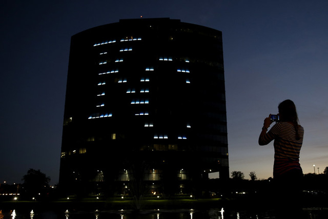 Allison Corley takes a photo of an office building displaying the logo for the Kansas City Royals baseball team Thursday, Oct. 16, 2014, in the Kansas City suburb of Overland Park, Kan. (AP Photo/ ...
