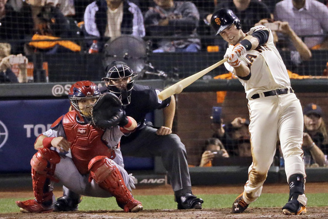 San Francisco Giants' Buster Posey hits an RBI single against the St. Louis Cardinals during the sixth inning of Game 4 of the National League baseball championship series Wednesday, Oct. 15, 2014 ...