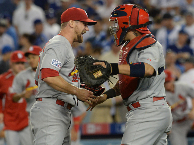 St. Louis Cardinals relief pitcher Trevor Rosenthal (26) and catcher Yadier Molina (4) celebrate the 10-9 victory against the Los Angeles Dodgers following game one of the 2014 NLDS playoff baseba ...