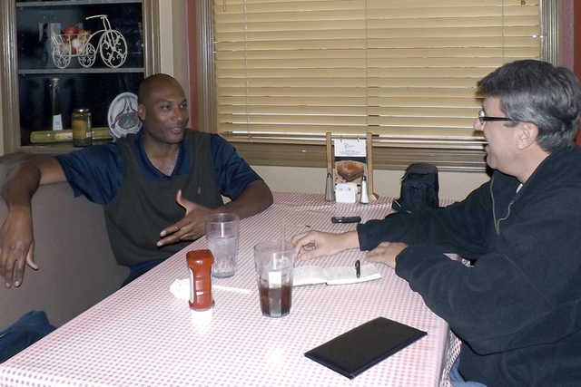 """Ed O' Bannon, left, is interviewed by author Rob Miech for the book, """"Eleventh Heaven,"""" about O' Bannon and the 1995 national hoops champion UCLA Bruins. (Courtesy Rob Miech)"""