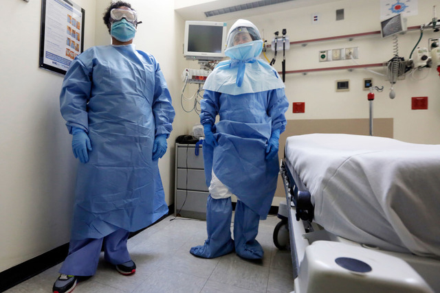 Bellevue Hospital nurse Belkys Fortune, left, and Teressa Celia, Associate Director of Infection Prevention and Control, pose in protective suits in an isolation room, in the Emergency Room of the ...
