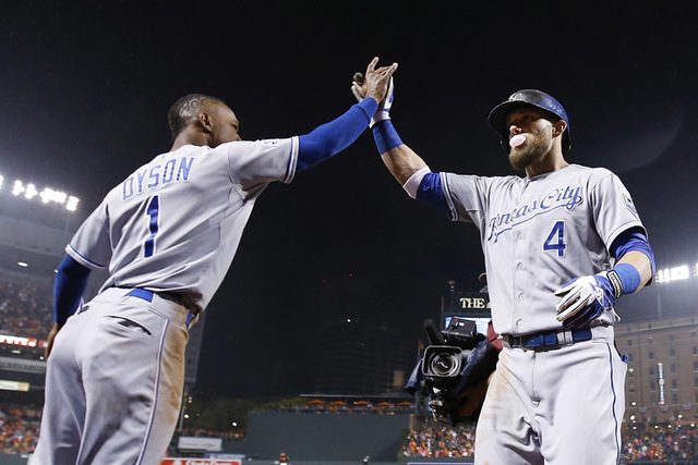 Kansas City Royals' Alex Gordon (4) celebrates with Jarrod Dyson (1) after hitting a solo home run during the 10th inning of Game 1 of the American League baseball championship series against the  ...