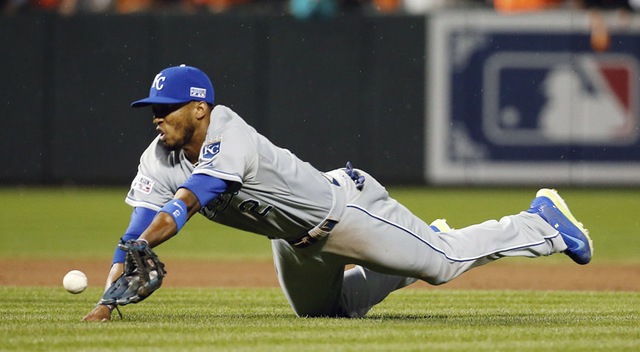 Kansas City Royals shortstop Alcides Escobar (2) dives for a ball hit by Baltimore Orioles' Alejandro De Aza during the sixth inning of Game 1 of the American League baseball championship series F ...