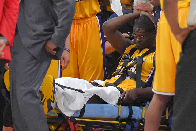 Los Angeles Lakers forward Julius Randle, right, sits on on a stretcher after Randle injured himself on a play during the second half of an NBA basketball game, Tuesday, Oct. 28, 2014, in Los Ange ...