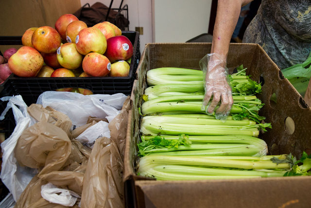 A woman hands out celery during the Westminster Presbyterian Church food bank, located at 4601 W. Lake Mead Blvd., on Friday, Sept. 26, 2014. The church is celebrating its 50th anniversary. (Saman ...