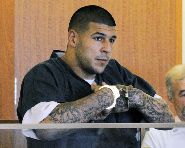 Former New England Patriots NFL football player Aaron Hernandez stands during a bail hearing in Superior Court in Fall River, Mass. Hernandez is accused of three murders in Massachusetts. Investig ...