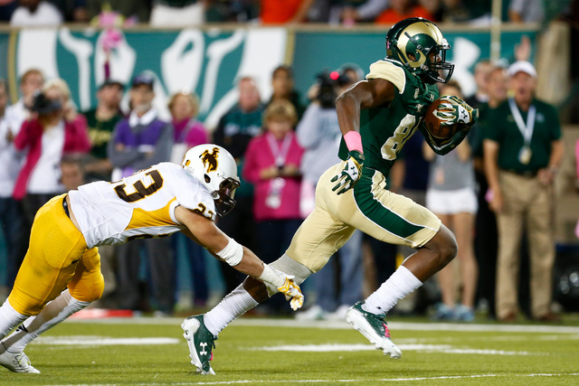 Wyoming Cowboys safety Tim Kamana (23) misses a tackle on Colorado State Rams wide receiver Xavier Williams (84) in the third quarter at Hughes Stadium in Fort Collins on Oct. 25, 2014. The Rams d ...