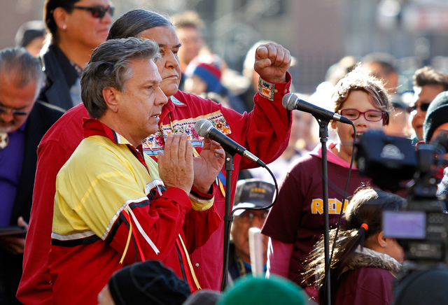 Nov 2, 2014; Minneapolis, MN, USA; David Glass and Clyde Bellecourt speak to protestors who oppose the name and imagery used by the Washington Redskins organization outside of TCF Bank Stadium bef ...