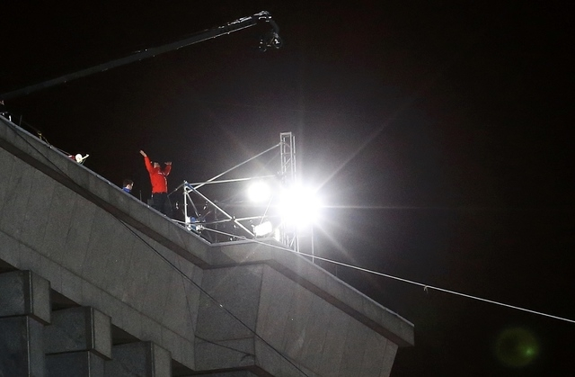 Daredevil Nik Wallenda reacts after completing his first walk along a tightrope between two skyscrapers suspended 500 feet above the Chicago River in Chicago, Sunday, Nov. 2, 2014. (Reuters/Jim Young)