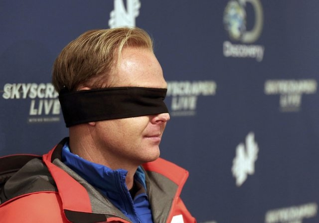 Daredevil Nik Wallenda wears his blindfold while answering questions about his blinfolded walk along a tightrope between two skyscrapers suspended 500 feet above the Chicago River in Chicago, Sund ...