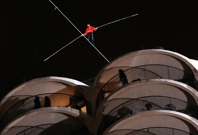 Daredevil Nik Wallenda walks along a tightrope between two skyscrapers suspended 500 feet above the Chicago River in Chicago, Sunday, Nov. 2, 2014. Wallenda did the high-wire walk twice, the secon ...