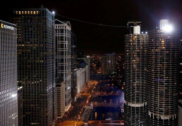 Daredevil Nik Wallenda walks along a tightrope between two skyscrapers suspended 500 feet above the Chicago River in Chicago, Sunday, Nov. 2, 2014. (Reuters/John Gress)