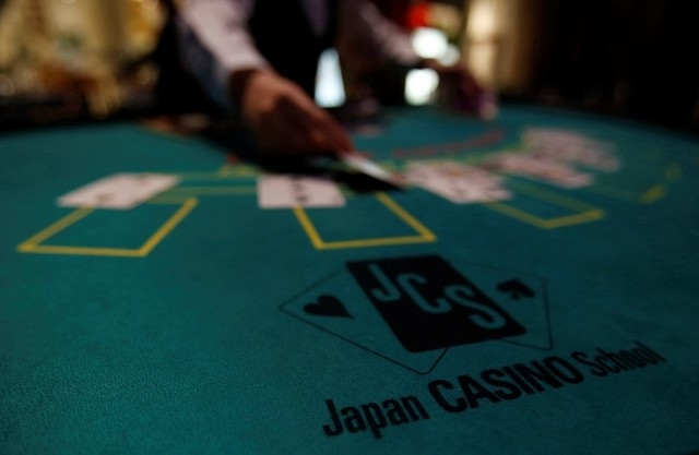 A logo of Japan casino school is seen as a dealer puts cards on a mock black jack casino table during a photo opportunity at an international tourism promotion symposium in Tokyo in this September ...