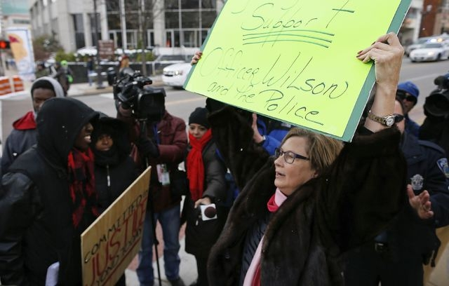 Pattie Canter (R), a supporter of police officer Darren Wilson, argues with supporters of Michael Brown during a demonstration in the streets in Clayton, Missouri, November 17, 2014. (Jim Young/Re ...