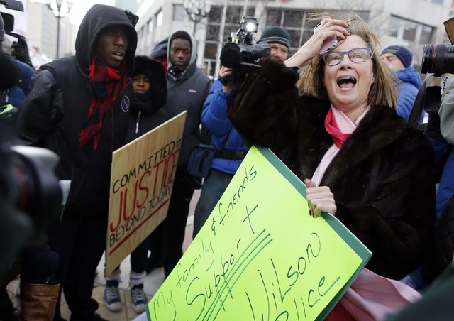 Pattie Canter (R), a supporter of police officer Darren Wilson, is confronted by supporters of Michael Brown during a demonstration in the streets in Clayton, Missouri, November 17, 2014. Several  ...