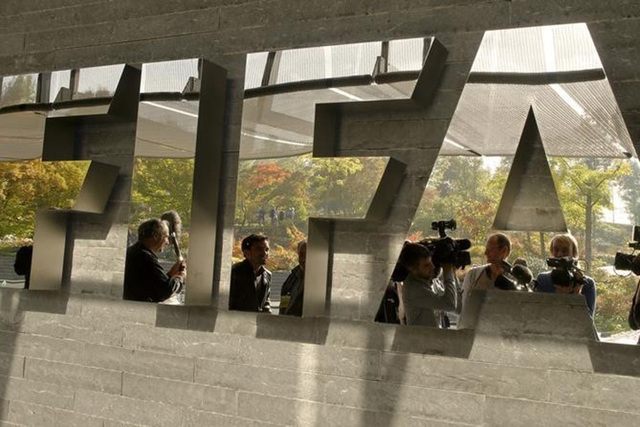 Journalists are reflected in a logo at the FIFA headquarters after a meeting of the executive committee in Zurich October 4, 2013. (REUTERS/Arnd Wiegmann)