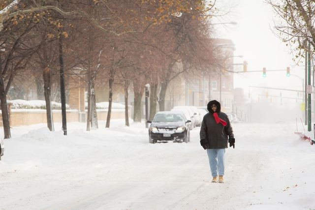 A woman walks down the middle of the street through the blowing snow in Buffalo, New York, November 19, 2014. (REUTERS/Lindsay DeDario)