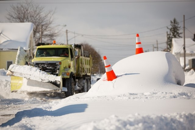 An abandon car marked by orange cones is buried under snow as a snowplow passes by in Buffalo, New York, November 19, 2014. (REUTERS/Lindsay DeDario)