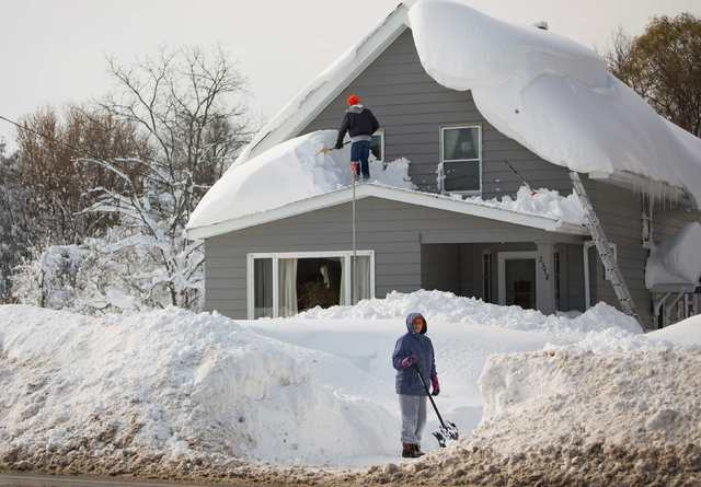 A man clears snow from his roof in the town of Cheektowaga near Buffalo, New York, November 19, 2014. (REUTERS/Lindsay DeDario)