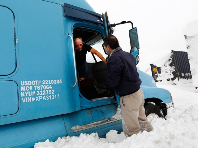 New York Governor Andrew Cuomo talks with a stranded trucker on interstate I-190 while surveying an area in West Seneca, New York November 19, 2014.  (REUTERS/Sharon Cantillon/Buffalo News/Pool)