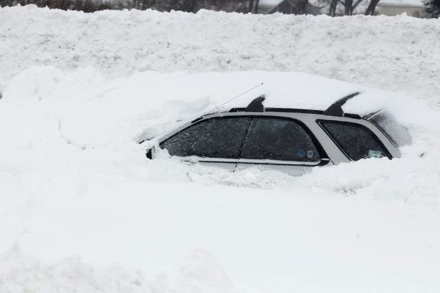 A vehicle is shown submerged in snow sits on interstate I-190 in West Seneca, New York November 19, 2014. (REUTERS/Sharon Cantillon/Buffalo News)