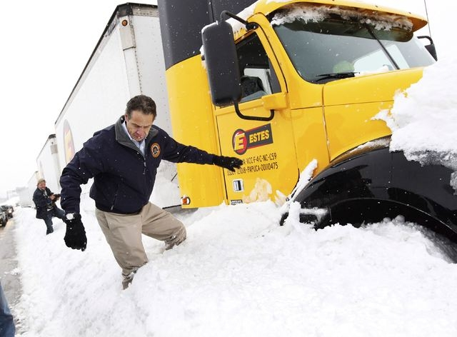 New York Governor Andrew Cuomo climbs over snow piled on the highway after talking with a stranded trucker on interstate I-190 while surveying an area in West Seneca, New York November 19, 2014.   ...