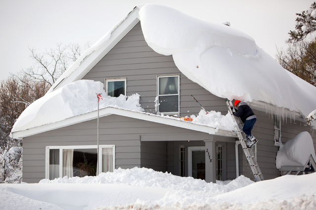 A man climbs on his roof to clear snow in the town of Cheektowaga near Buffalo, New York, November 19, 2014.  (REUTERS/Lindsay DeDario )