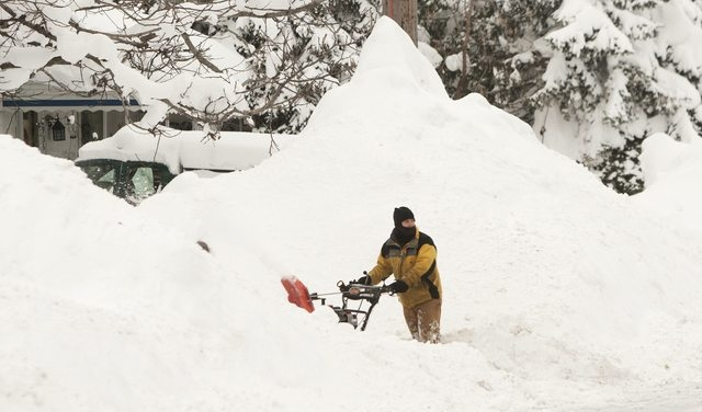 A man clears his driveway of snow following an autumn snow storm in Buffalo, New York November 20, 2014. (REUTERS/Aaron Lynett)