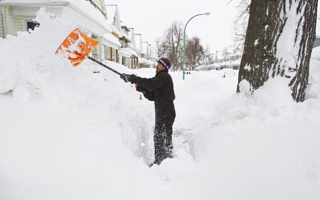 Michael Peters shovels snow from his sidewalk following An autumn storm in Buffalo, New York November 20, 2014. (REUTERS/Aaron Lynett)