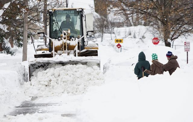 Heavy machinery clears snow from a street following an autumn storm in Buffalo, New York, November 20, 2014. (REUTERS/Aaron Lynett)