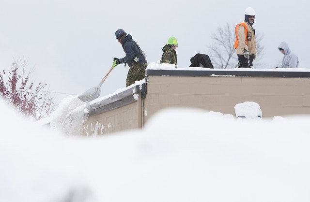 Workers shovel snow from a roof following an autumn storm in Buffalo, New York November 20, 2014. (REUTERS/Aaron Lynett)