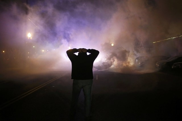 A protester stands with his hands on his head as a cloud of tear gas approaches after a grand jury returned no indictment in the shooting of Michael Brown in Ferguson, Missouri, November 24, 2014. ...