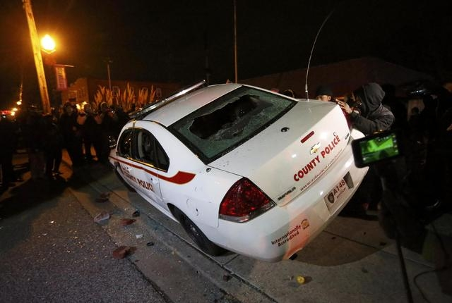 Protesters rock a vandalized police car  in Ferguson, Missouri, after a grand jury returned no indictment in the shooting of Michael Brown November 24, 2014. A St. Louis County grand jury chose no ...