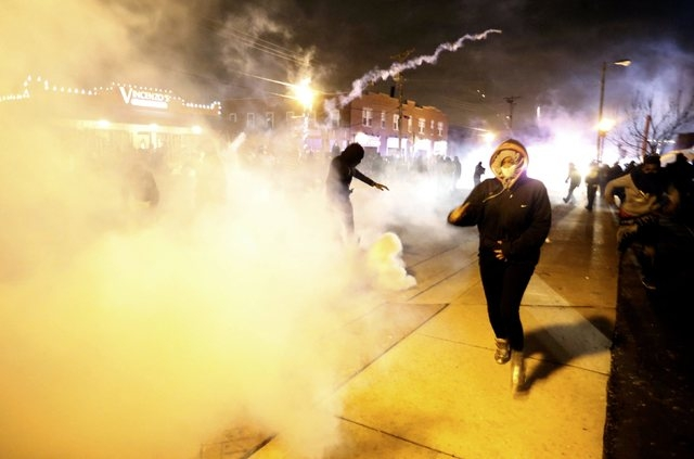 Protesters run from a cloud of tear gas after a grand jury returned no indictment in the shooting of Michael Brown in Ferguson, Missouri, November 24, 2014. A St. Louis County grand jury chose not ...
