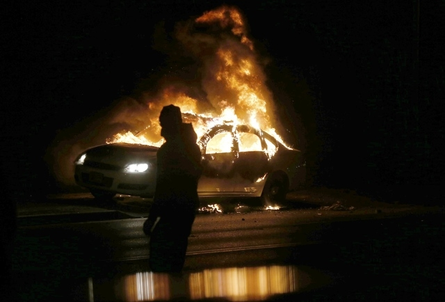 A car burns on the street after a grand jury returned no indictment in the shooting of Michael Brown in Ferguson, Missouri November 24, 2014. Gunshots were heard and bottles were thrown as anger r ...