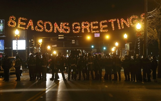 Police form a line in the street under a holiday sign after a grand jury returned no indictment in the shooting of Michael Brown in Ferguson, Missouri November 24, 2014. Gunshots were heard and bo ...