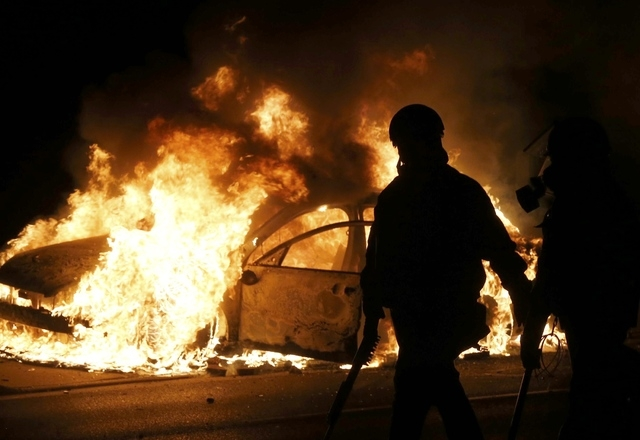 Police walk past a burning police car on the street after a grand jury returned no indictment in the shooting of Michael Brown in Ferguson, Missouri November 24, 2014. Gunshots were heard and bott ...