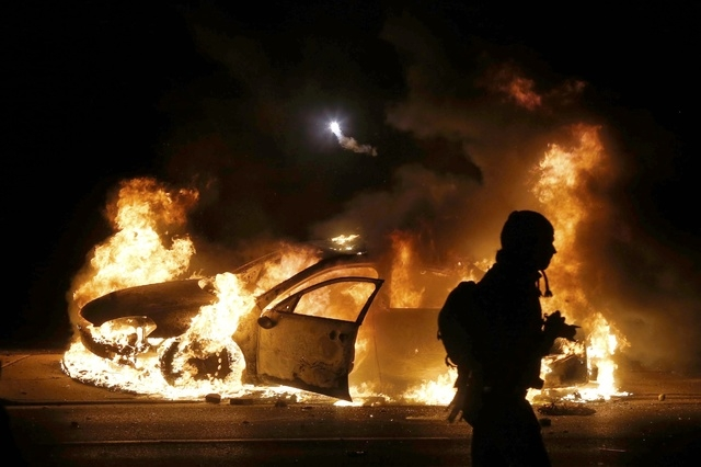 A police car burns on the street after a grand jury returned no indictment in the shooting of Michael Brown in Ferguson, Missouri November 24, 2014. (REUTERS/Jim Young)